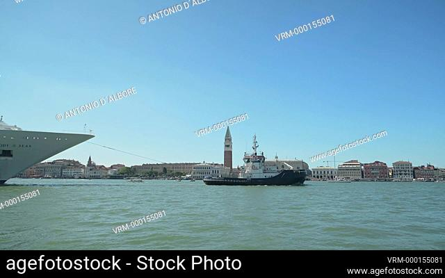 A tugboat towing a cruise ship in Grand Canal. Venice. Italy