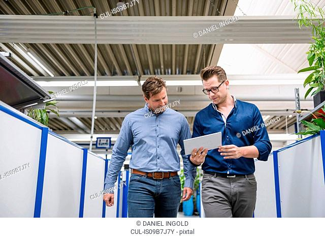 Factory managers walking and looking at digital tablet in factory corridor