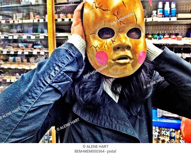 Caucasian woman wearing Halloween mask in store