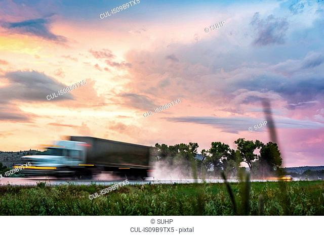 Vehicle travelling on wet highway at sunset, Montana, US
