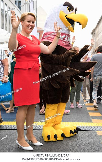 """17 August 2019, Berlin: Franziska Giffey (SPD), Federal Minister for Family Affairs, dances with the mascot of the """"""""Children's Ministry"""""""" as part of the """"""""Open..."""