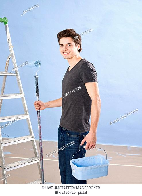 Young painter holding a paint roller and a paint bucket in front of a ladder