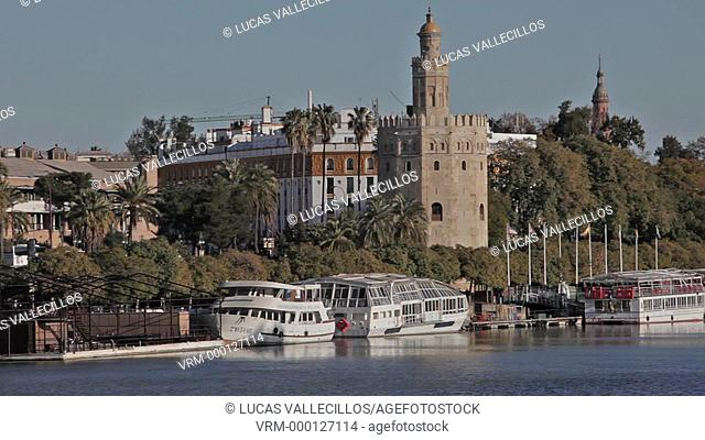 Gold tower in Guadalquivir river. In the background towers of España square. Seville, Andalusia, Spain