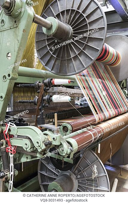 Spoked industrial cylinders feeding brightly coloured yarns into a jacquard weaving loom, La Manufacture de Roubaix, France