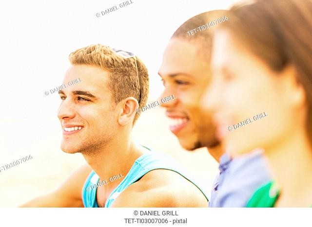 Portrait of young man with defocused view of friends in foreground