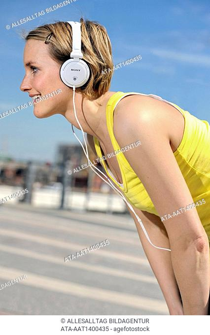 Jogging woman with headphones takes a break