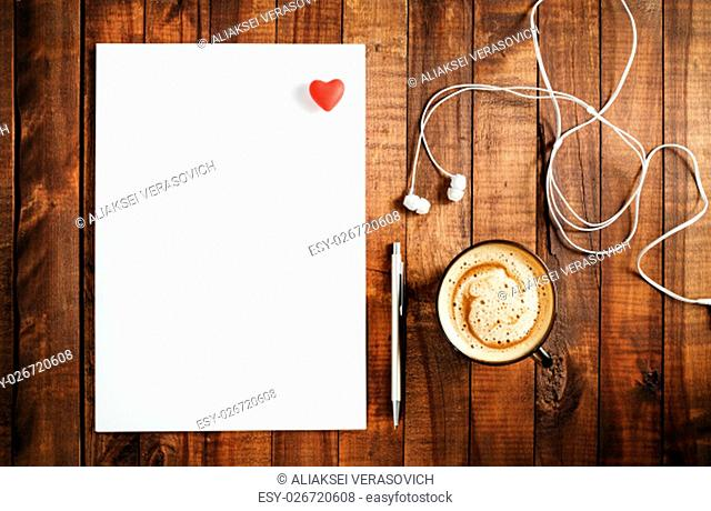 Blank branding template on vintage wooden table background. Blank white paper, letterhead, pen, headphones and red heart