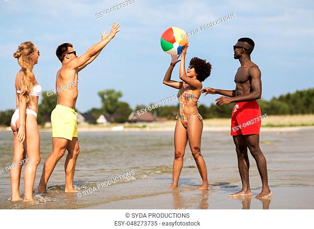 friends playing with beach ball in summer