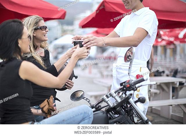 Woman on motorcycle getting coffee from waiter with her friend