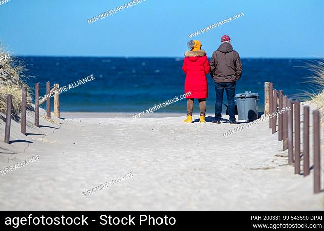 31 March 2020, Mecklenburg-Western Pomerania, Rostock-Warnemünde: Two walkers are standing on a beach access and look out over the Baltic Sea