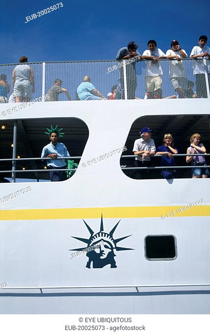 Circle Line ferry to Liberty Island with passengers leaning over the sides