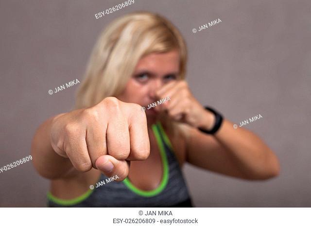 Dangerous female fighter posing, focus on the fist