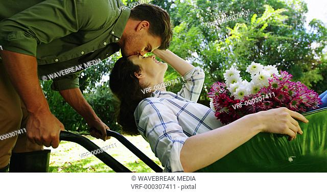 Man kissing woman in wheelbarrow in garden
