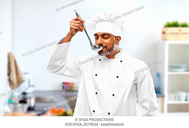 indian chef tasting food from ladle at kitchen
