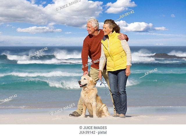 Senior couple with dog on sunny beach