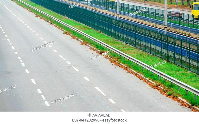 An asphalted city road with markings and a fence of a high-speed tramway in the city