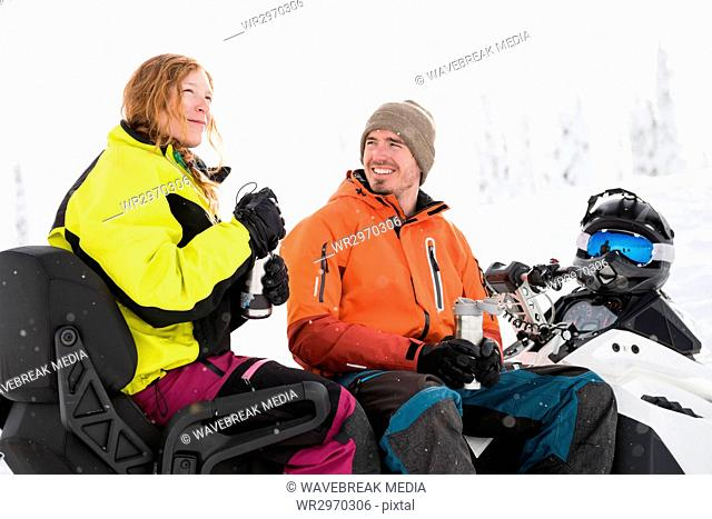Couple having coffee from thermos while relaxing on snowmobile