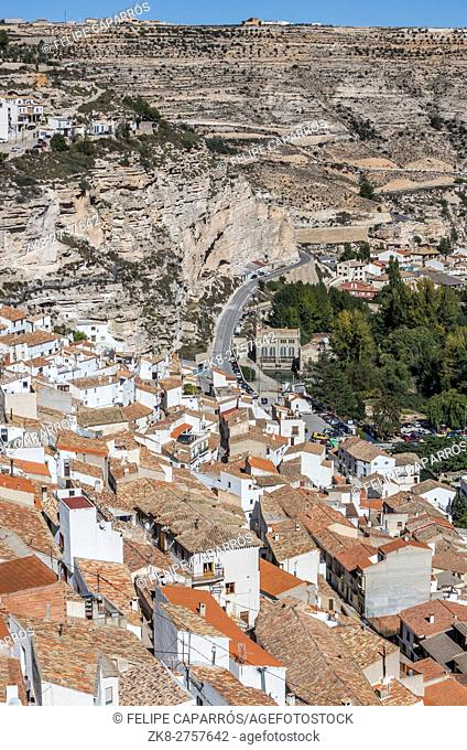 Houses and roofs next to mountain limestone, view to the mountains of the river Jucar, take in Alcala of the Jucar, Albacete province, Spain