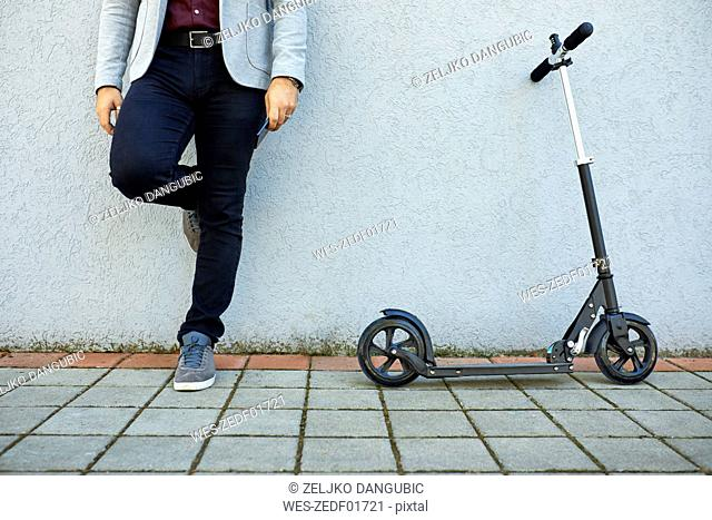 Low section of businessman with scooter and cell phone leaning against a wall