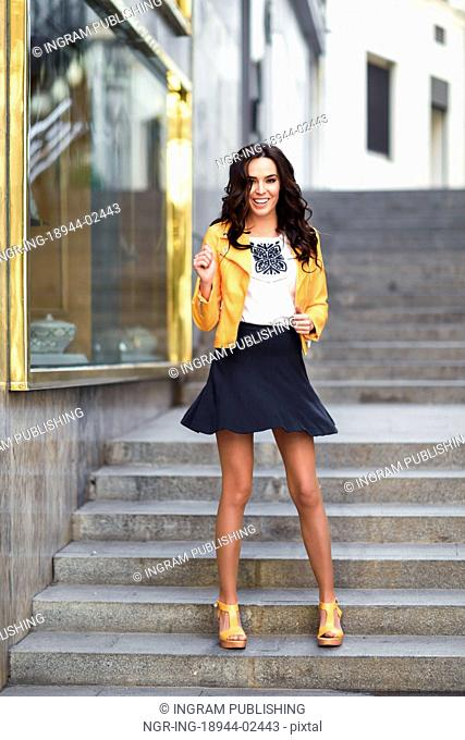 Young brunette woman, model of fashion, wearing orange modern jacket and blue skirt. Pretty caucasian girl with long wavy hairstyle smiling