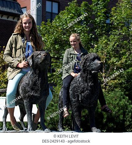 Two teenage girls pose sitting atop dog statues; St. John's, Newfoundland, Canada