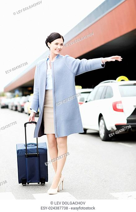 travel, business trip, people, gesture and tourism concept - smiling young woman with travel bag catching taxi at airport terminal or railway station