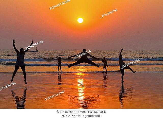 Three boys jumping on the beach during sunset