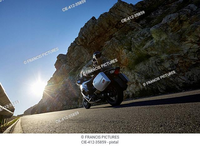 Couple riding motorcycle on sunny road along craggy cliff