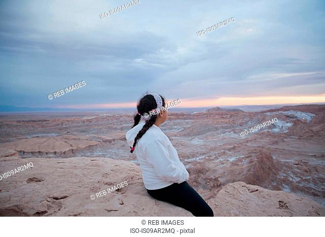 Young girl sitting on rock looking at view, Valley of the Moon, San Pedro. Atacama. Chile