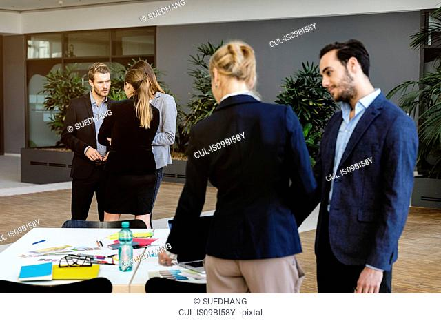 Businesswoman and man in office discussing design swatches on table