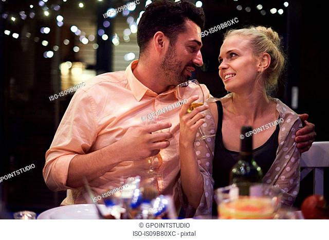 Couple sitting at table, holding wine glasses, face to face, smiling