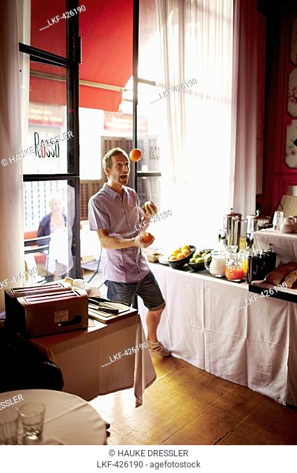 Man juggling with fruits inside a hotel breakfast room, Barcelona, Catalonia, Spain