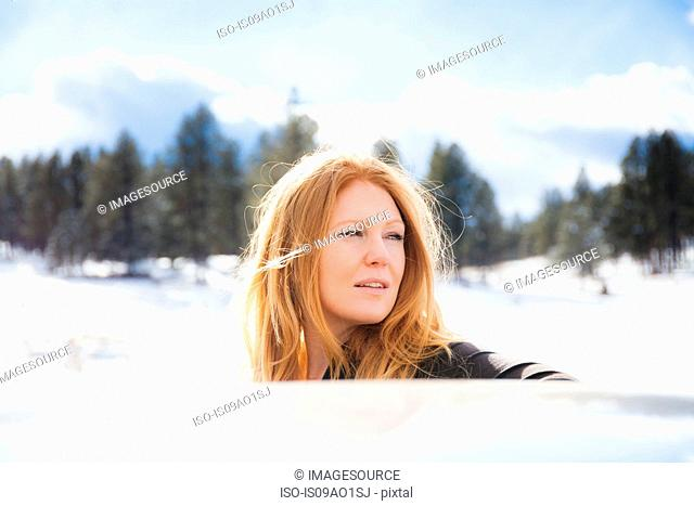 Portrait of mid adult woman gazing over car roof in snow covered landscape