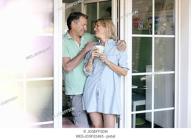 Happy mature couple standing at French window