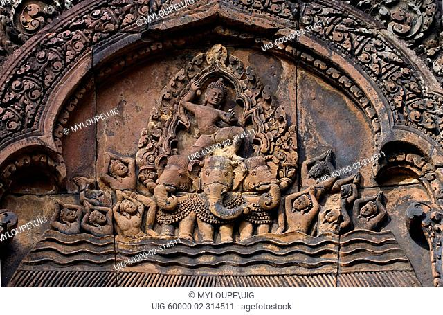 Bas relief in red sandstone of Indra riding his three headed elephant on the East Pediment of the North Library at Banteay Srei