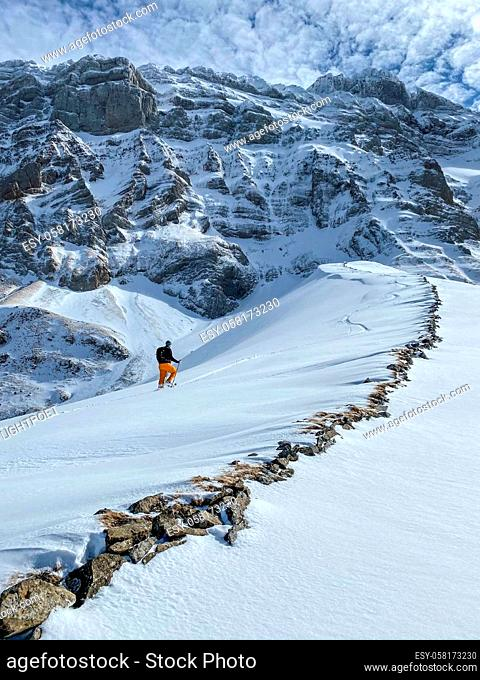 Winter sports - young man walking with snowshoes uphill in high mountains covered with lots of snow