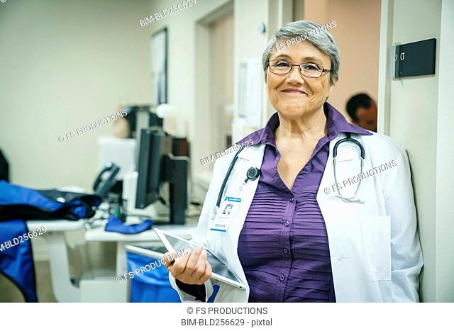 Portrait of smiling mixed race doctor holding digital tablet
