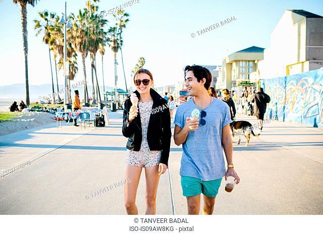 Young couple strolling eating ice cream cones, Venice Beach, California, USA