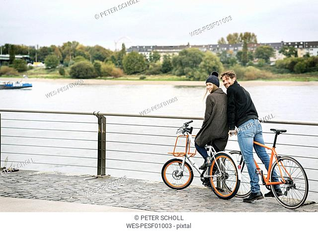 Smiling couple with bicycles at the riverside