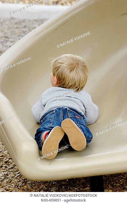 Rear view of toddler on slide