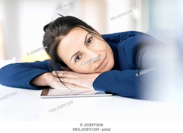 Portrait of businesswoman leaning on desk