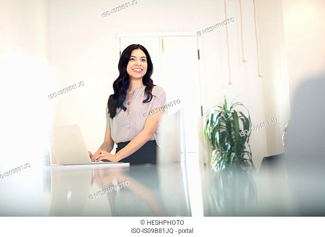 Young businesswoman typing on laptop at desk
