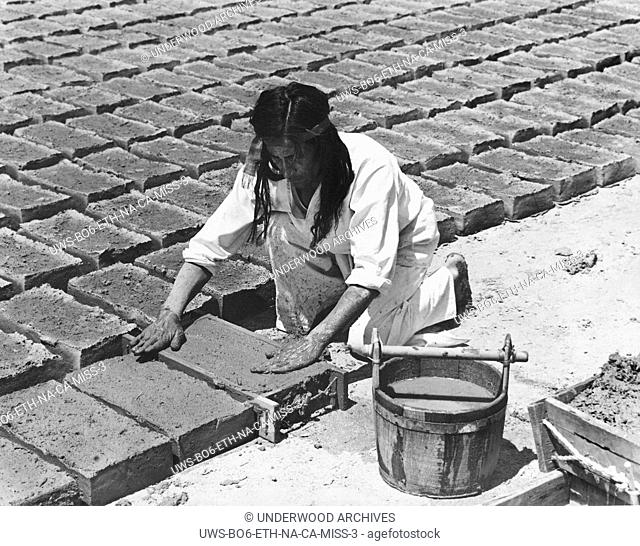 California: c. 1930 .The padres taught the Indians to make the adobe bricks used in the building of the missions. When the mold was full the mud was patted...