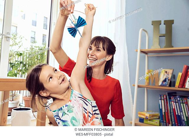 Mother and daughter playing with self-made paper bird