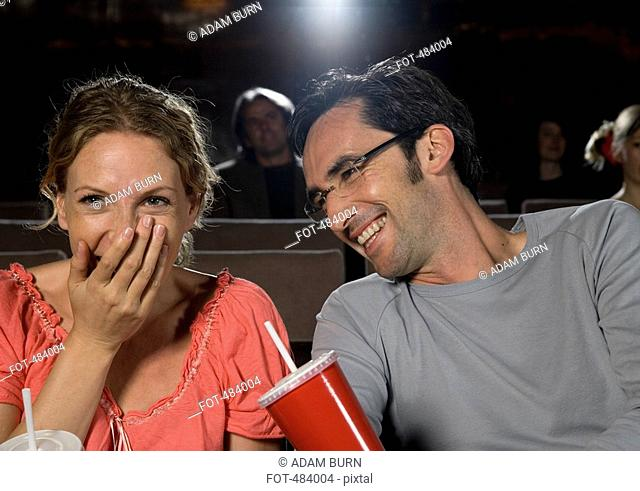 A mid adult couple laughing in a movie theater