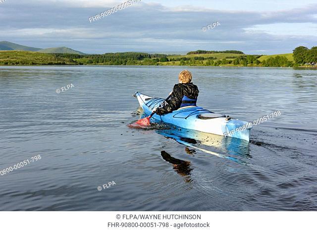 Boy kayaking on reservoir, Killington Lake, Killington Beck, Cumbria, England, June