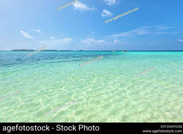 Empty tropical beach background. Horizon with resort island, sky and white sand under clear water in Maldives