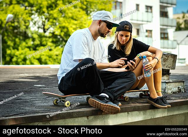 boy and girl on a skateboard are sitting and watching something on the mobile phone on a summer day