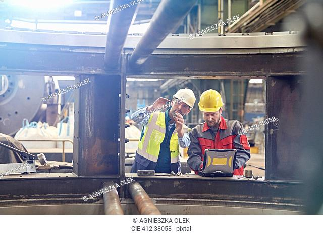 Male engineers with laptop examining parts in factory