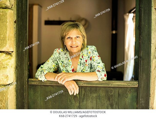 A woman, 65, smiling at a doorway in Milia Mountain Retreat, Chania, Crete, Greece